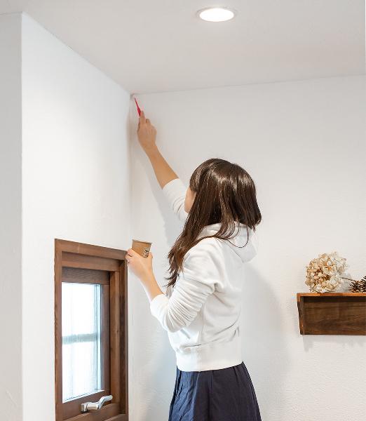 女性が漆喰の壁をメンテナンスしている画像