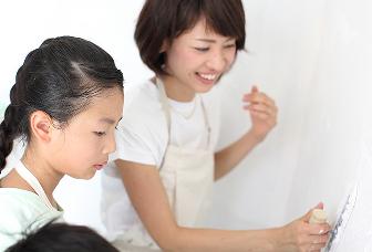 女性と子供が漆喰の壁をメンテナンスしている画像